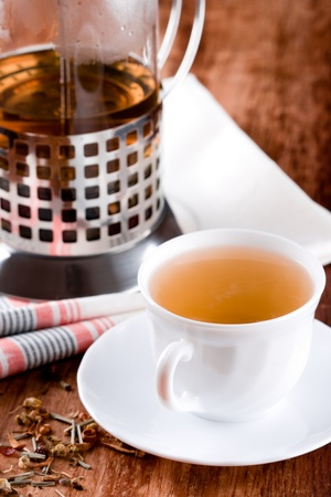 french press and cup of fresh herbal tea closeup on wooden table photo