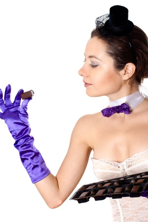 portrait of young attractive woman in corset and little hat eating sweets on white background photo