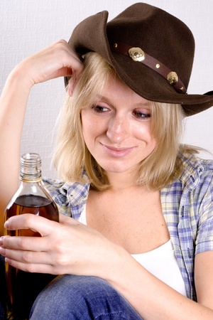 pretty western woman in cowboy shirt and hat with bottle of whiskey photo