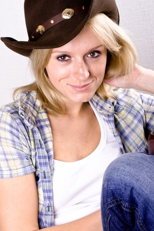 pretty western woman in cowboy shirt and hat isolated on white background photo