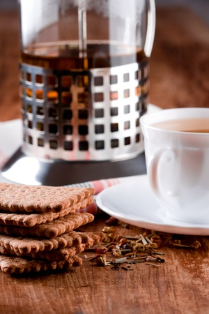 french press, cup of herbal tea and some fresh cookies closeup on wooden table  photo