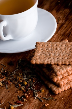 cup of fresh herbal tea and some cookies closeup on wooden table photo