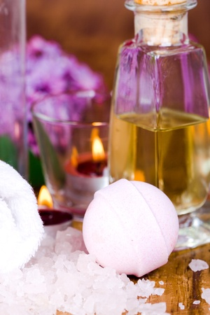 bath and spa items (towel, oil, lilac, sea salt, candles) on wooden background photo