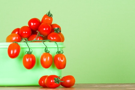 container with fresh tomatoes closeup on green background photo