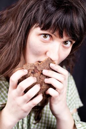 portrait of a poor beggar woman eating bread in her hands Stock Photo - 9255128