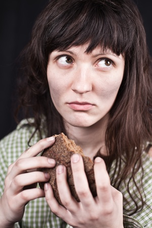 portrait of a poor beggar woman with a piece of bread in her hands Stock Photo - 9255127