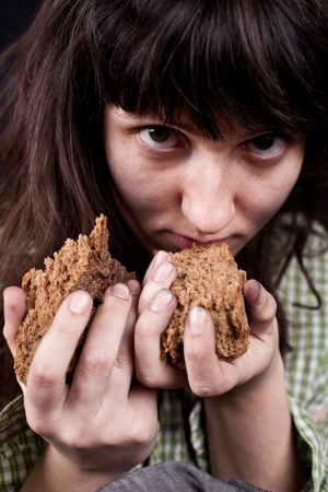 portrait of a poor beggar woman with a piece of bread in her hands Stock Photo - 9355756