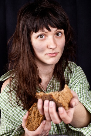 portrait of a poor beggar woman with a piece of bread in her hands Stock Photo - 9355758