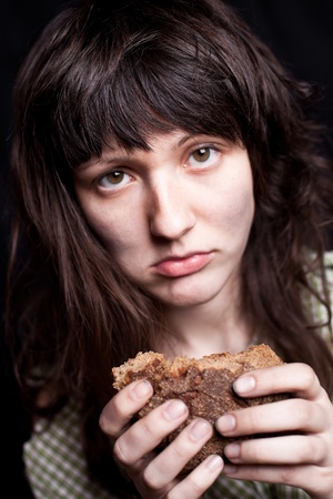 portrait of a poor beggar woman with a piece of bread in her hands Stock Photo - 9389475