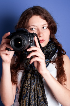 beautiful woman-photographer going to make picture on blue background.  Stock Photo - 9389480