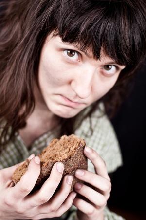 portrait d'une femme pauvre mendiant avec un morceau de pain dans ses mains Banque d'images - 9586353