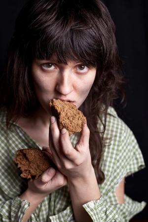 portrait of a poor beggar woman eating bread in her hands Stock Photo - 10024065