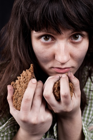 portrait of a poor beggar woman with a piece of bread in her hands Stock Photo - 11181996