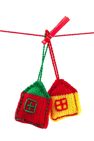 house warming: two knitted colorful houses on a red string isolated on white background
