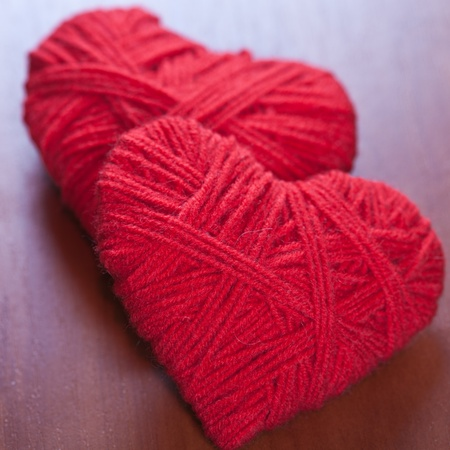 two red thread hearts closeup on wooden background photo