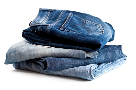 stack of four variety of jeans on white background  photo