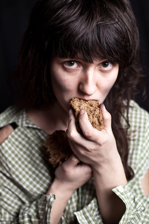 portrait of a poor beggar woman eating bread in her hands photo