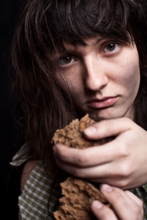 beggary: portrait of a poor beggar woman with a piece of bread in her hands Stock Photo