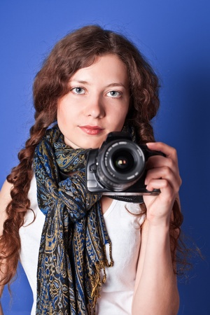 shootting: beautiful woman-photographer going to make picture on blue background.  Stock Photo