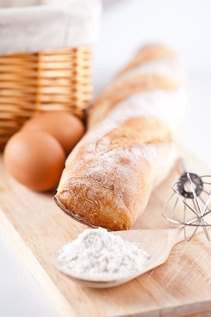 still life of bread, flour, eggs and kitchen utensil on a wooden board  photo