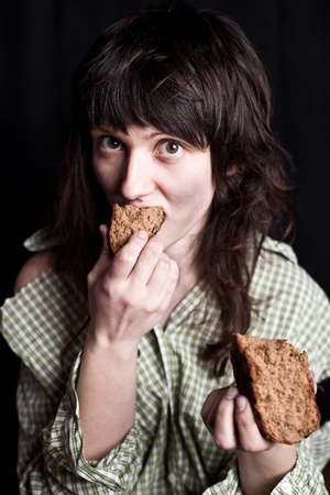 portrait of a poor beggar woman eating bread in her hands Stock Photo - 12508384