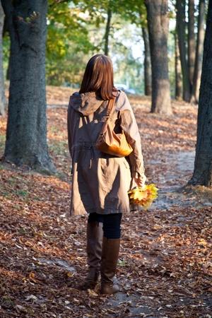 bata blanca: mujer que caminaba en el Parque de otoño