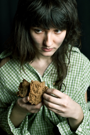 portrait of a poor beggar woman with a piece of bread in her hands photo