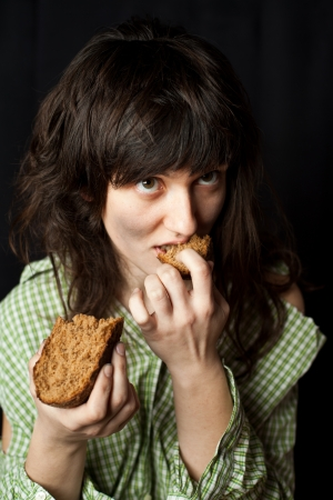portrait of a poor beggar woman eating bread  Stock Photo - 14977336