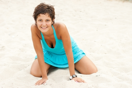 portrait of attractive brunet woman in blue sitting on a sand photo