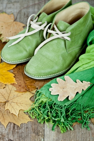pair of green leather boots, scarf and yellow leaves on rustic wooden floor Stock Photo - 15235959