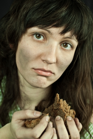 misery: portrait of a poor beggar woman with a piece of bread in her hands Stock Photo