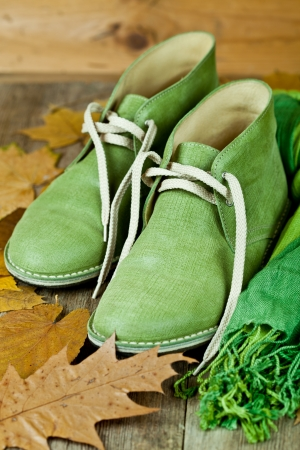pair of green leather boots, scarf and yellow leaves on rustic wooden floor  photo