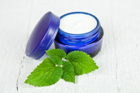 urtica: face cream in blue jar with green leaf of urtica on white wooden background Stock Photo