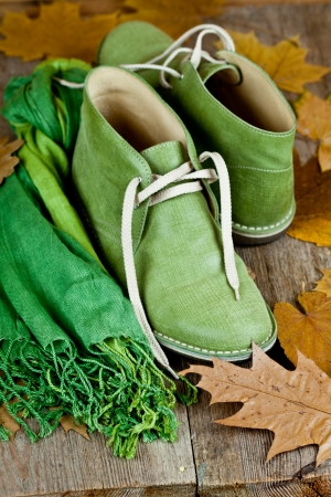 pair of green leather boots, scarf and yellow leaves on rustic wooden floor Stock Photo - 15989010
