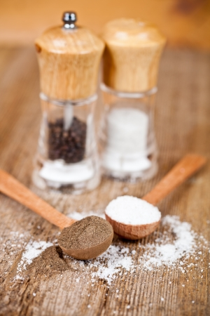 salt and pepper in spoons and shakers on rustic wooden table photo