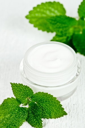 urtica: face cream in jar with urtica closeup on white wooden background