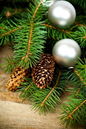christmas fir tree with pinecones and decorations on a wooden board photo