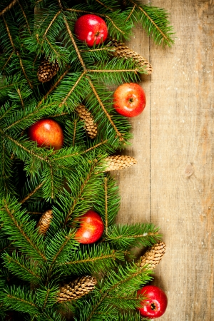 christmas fir tree with pinecones and apples on a wooden board photo