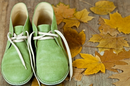 pair of green leather boots and yellow leaves on an old wooden floor Stock Photo - 16172813