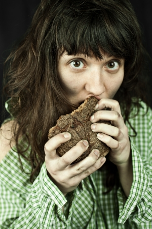 portrait of a poor beggar woman eating bread in her hands Stock Photo - 16129923