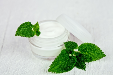 urtica: face cream in glass jar with green leaf of urtica on white wooden background