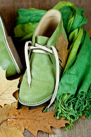 pair of green leather boots, scarf and yellow leaves on rustic wooden floor Stock Photo - 16172841