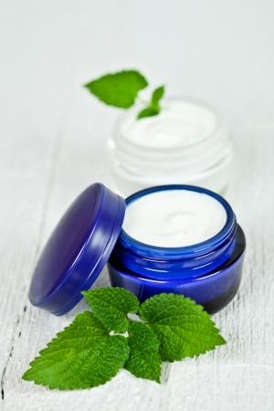 urtica: face cream in jars with urtica leaves closeup on white wooden background