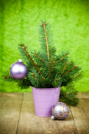 bucket with christmas fir tree and purple decorations on a wooden board photo