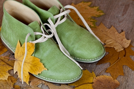 pair of green leather boots and yellow leaves on an old wooden floor  photo