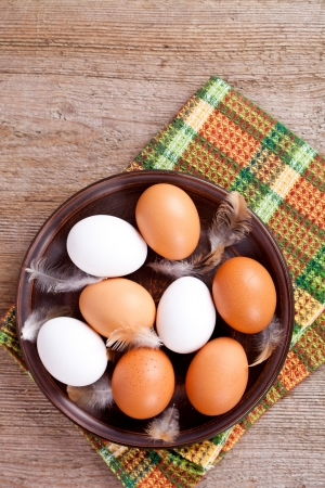 eggs in a plate, towel and feathers on rustic wooden table photo