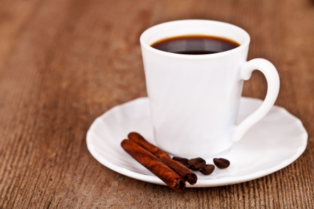 cup of coffee and cinnamon on rustic wooden table photo