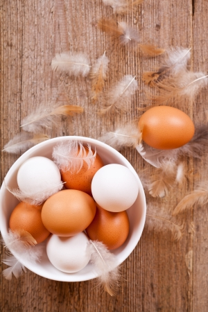 brown and white eggs in a bowl, feathers on rustic wooden table photo