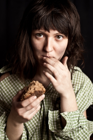beggary: portrait of a poor beggar woman eating bread