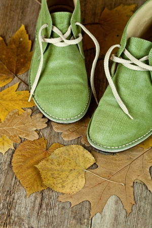 road autumnal: pair of green leather boots and yellow leaves on an old wooden floor  Stock Photo
